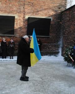 Petro Fedorowicz Miszczuk z flagą Ukrainy na dziedzińcu bloku 11, przed ścianą straceń